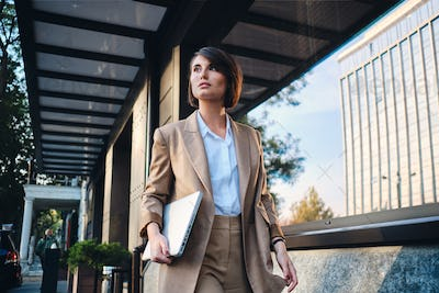 Young attractive stylish businesswoman with laptop thoughtfully walking on street