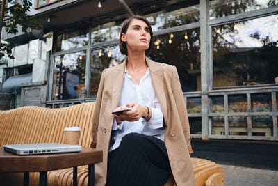 Young gorgeous stylish businesswoman with cellphone intently looking away in cafe on street