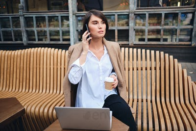 Young confident stylish businesswoman with laptop talking on cellphone during coffee break in cafe