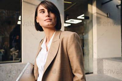 Portrait of young beautiful stylish businesswoman with laptop dreamily looking away on street