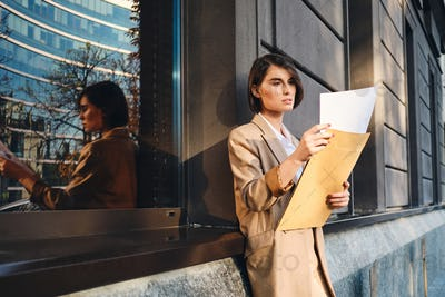 Young confident stylish businesswoman thoughtfully working with papers outdoor