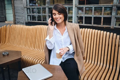 Young pretty businesswoman with laptop joyfully talking on cellphone in cafe on street