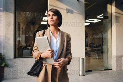 Young attractive stylish businesswoman with laptop dreamily looking away on street