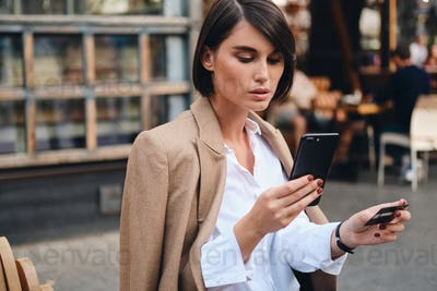 Young beautiful stylish businesswoman with credit card confidently using cellphone in cafe on street