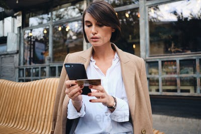 Confident stylish businesswoman with credit card thoughtfully using cellphone in cafe on street