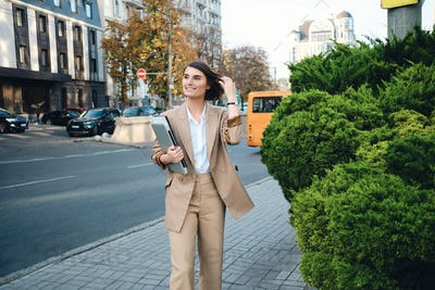 Young attractive positive businesswoman in beige suit with laptop happily walking on city street