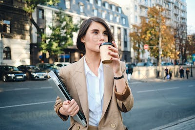 Young pretty businesswoman with laptop drinking coffee during break  on city street