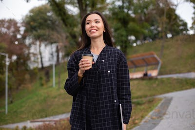 Young attractive casual woman in coat with coffee to go and laptop happily walking in city park