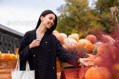 Young attractive casual woman at farm shop happily looking for pumpkin for Halloween day outdoor