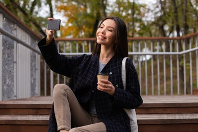 Young beautiful casual woman with coffee to go happily taking selfie on cellphone in autumn park