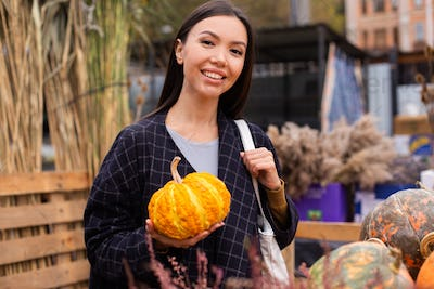 Asian attractive woman happily buying pumpkin for Halloween day at autumn farm shop outdoor