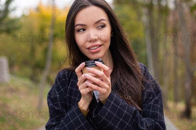 Portrait of young attractive woman in coat with coffee to go slyly looking away in autumn park
