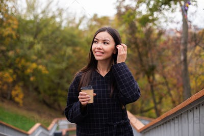 Young pretty smiling woman in coat with coffee to go happily looking aside in park