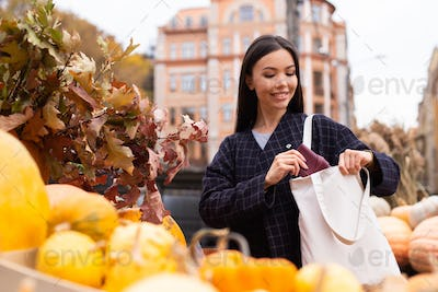 Portrait of young smiling casual woman happily looking for purse in bag at autumn farm shop outdoor