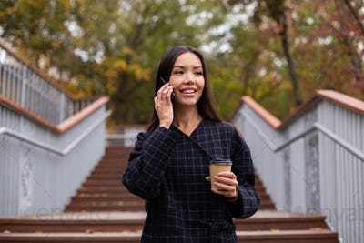 Young pretty casual woman in coat with coffee to go talking on cellphone happily walking in park