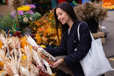 Young beautiful woman happily buying colorful corn for Halloween day at autumn farm shop outdoor