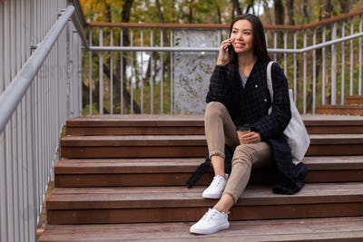 Young beautiful casual woman with coffee to go happily talking on cellphone on stairs in park