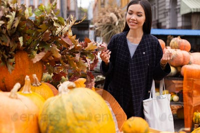 Young attractive smiling woman at farm shop happily looking for pumpkin for Halloween day outdoor