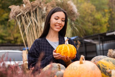 Young attractive smiling casual woman happily buying pumpkin at autumn farm shop outdoor