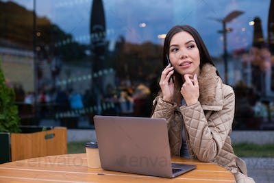 Young confident woman in down jacket with laptop thoughtfully talking on cellphone in cafe on street