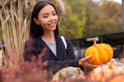 Young attractive casual woman joyfully buying pumpkin for Halloween day at autumn farm shop outdoor