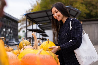 Young attractive woman happily buying pumpkin for Halloween day at autumn farm shop outdoor