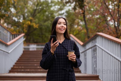 Young pretty casual woman in coat with coffee to go and cellphone happily looking away in city park