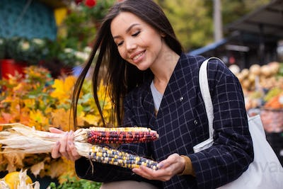 Young attractive casual woman joyfully buying colorful corn at autumn farm shop outdoor