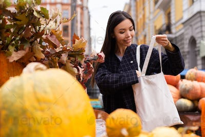Young attractive casual woman happily buying pumpkin at autumn farm shop outdoor