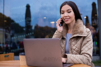 Smiling confident woman in down jacket working on laptop happily talking on cellphone in cafe