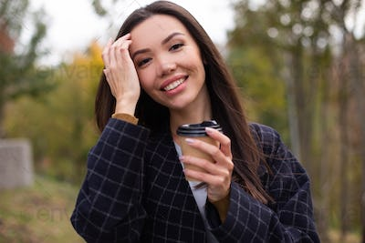 Portrait of young joyful woman in coat with coffee to go happily looking in camera in autumn park