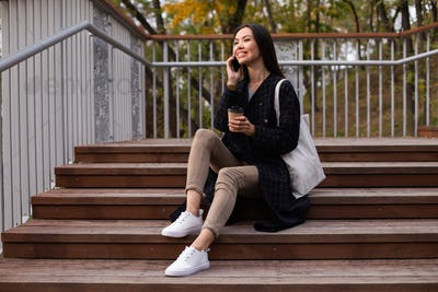 Young attractive woman with coffee to go joyfully talking on cellphone sitting on stairs in park