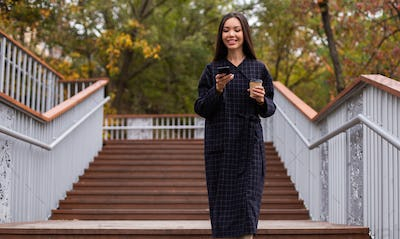 Young attractive casual woman in coat with coffee joyfully using cellphone walking in city park