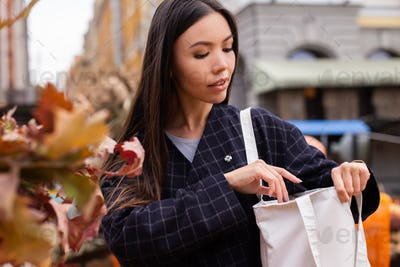 Young beautiful woman thoughtfully looking for purse in bag at autumn farm shop outdoor