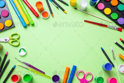 Colorful paints set on green color background, top view