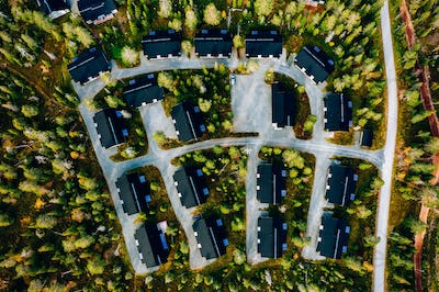 Aerial view of cottage village with colorful trees in autumn season forest in rural Finland.