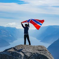 Woman with a waving flag of Norway on the background of nature