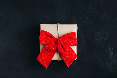 Christmas gift box. Christmas present box with red ribbon bow on dark stone background.