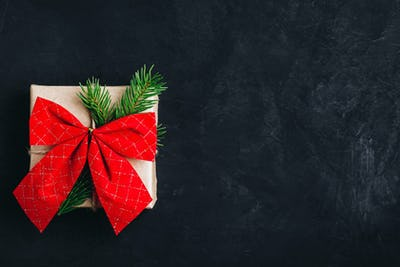 Christmas gift box. Christmas present box with red  bow and tree branch on dark stone background.
