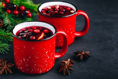 Traditional Christmas Mulled Wine drink with cranberries, orange slices and spices in red mugs