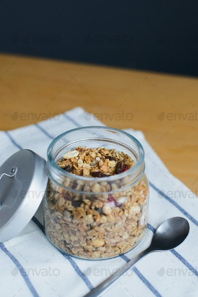 baked muesli with peanuts, hazelnuts, oat and wheat flakes in glass jar