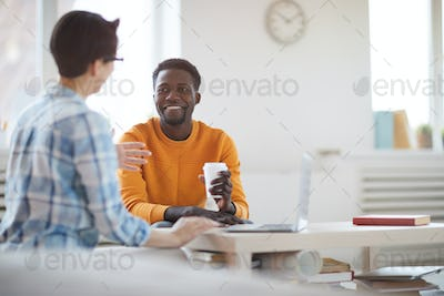 Smiling African Man Talking to Colleague in Office