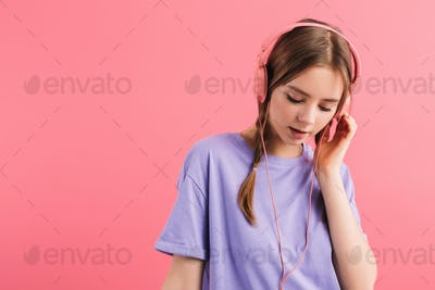 Young dreamy girl with two braids in lilac t shirt thoughtfully listening music in headphones