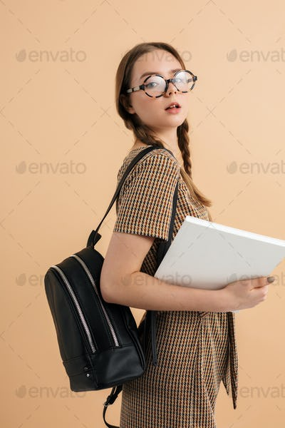 Young school girl with braids in tweed jumpsuit and eyeglasses holding book looking in camera