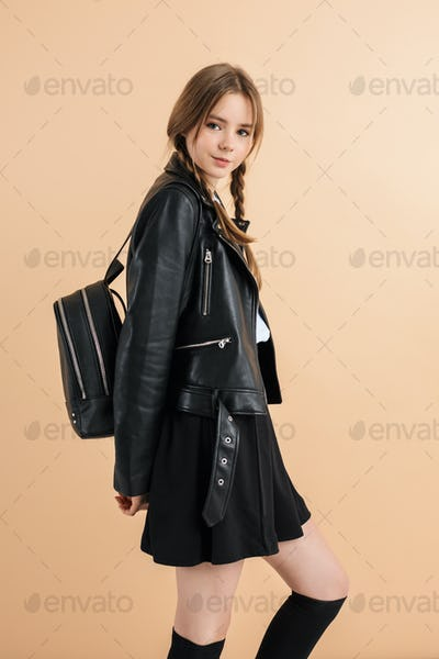 Young smiling school girl with braids in leather jacket and skirt happily looking in camera