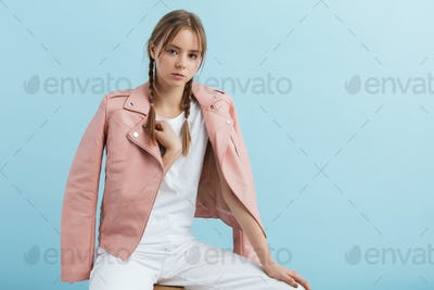 Young attractive pensive girl with braids in pink leather jacket dreamily looking in camera