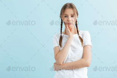 Young girl with braids in white t-shirt holding hand near face thoughtfully looking in camera