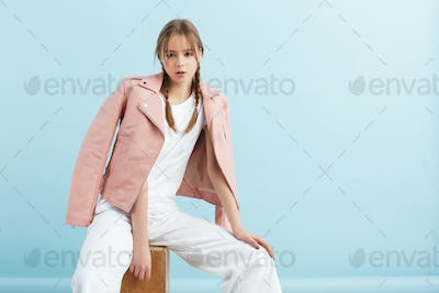 Young beautiful girl with braids in pink leather jacket dreamily posing at studio