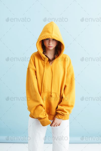 Young beautiful girl with two braids in orange hoodie and white jeans thoughtfully looking in camera