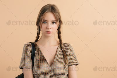 Young beautiful school girl with braids in tweed dress thoughtfully looking in camera